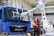 Woman works with roboter on truck